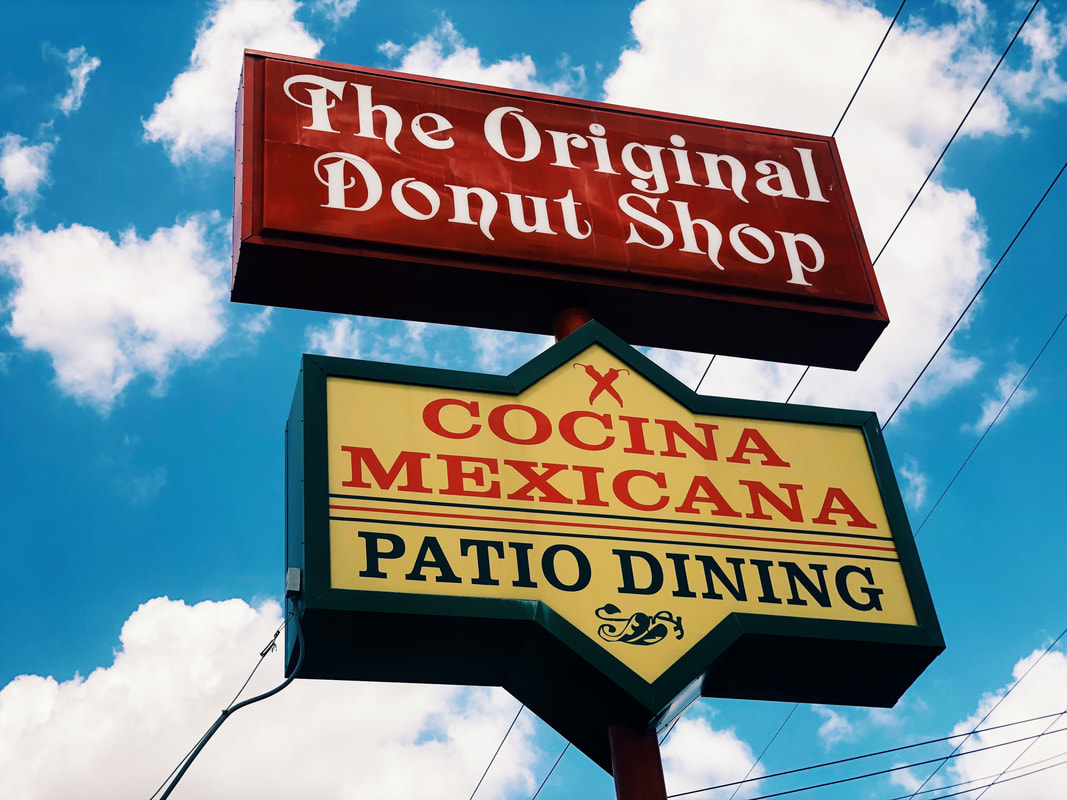 Two signs for the Original Donut Shop against a blue sky with clouds